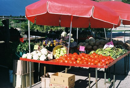 Red and white vegetables under red awning / tent