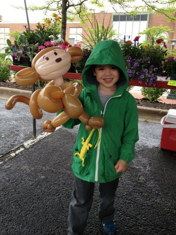 Boy in green sweatshirt with monkey balloon