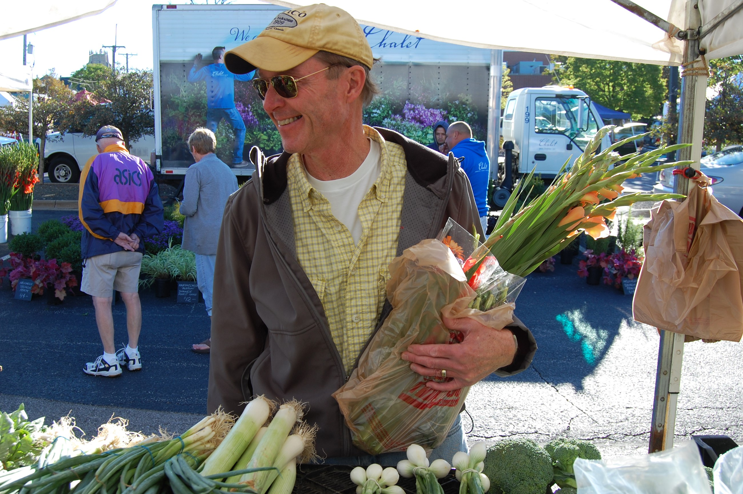 Man in sunglasses holding purchased produce