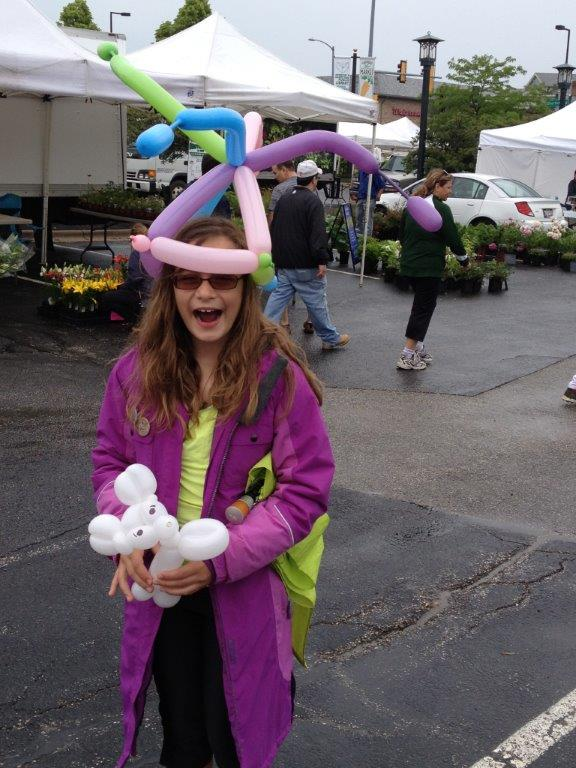 Young girl with balloon hat and small balloon animal