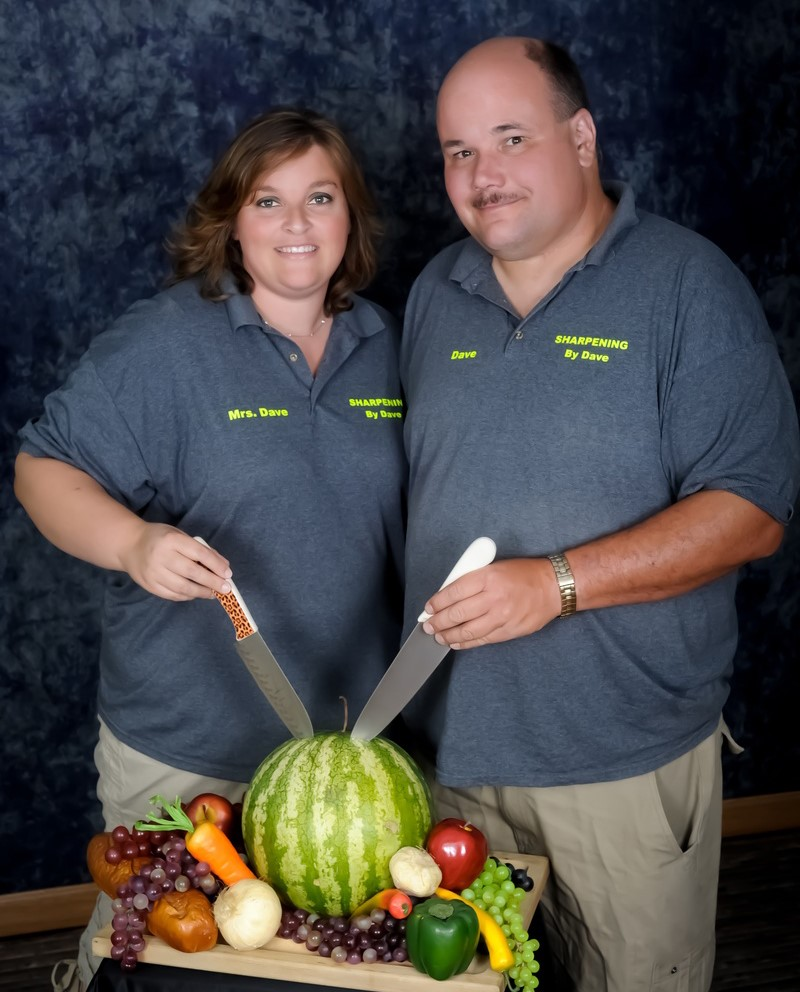Dave and a woman showing knives next to fruit
