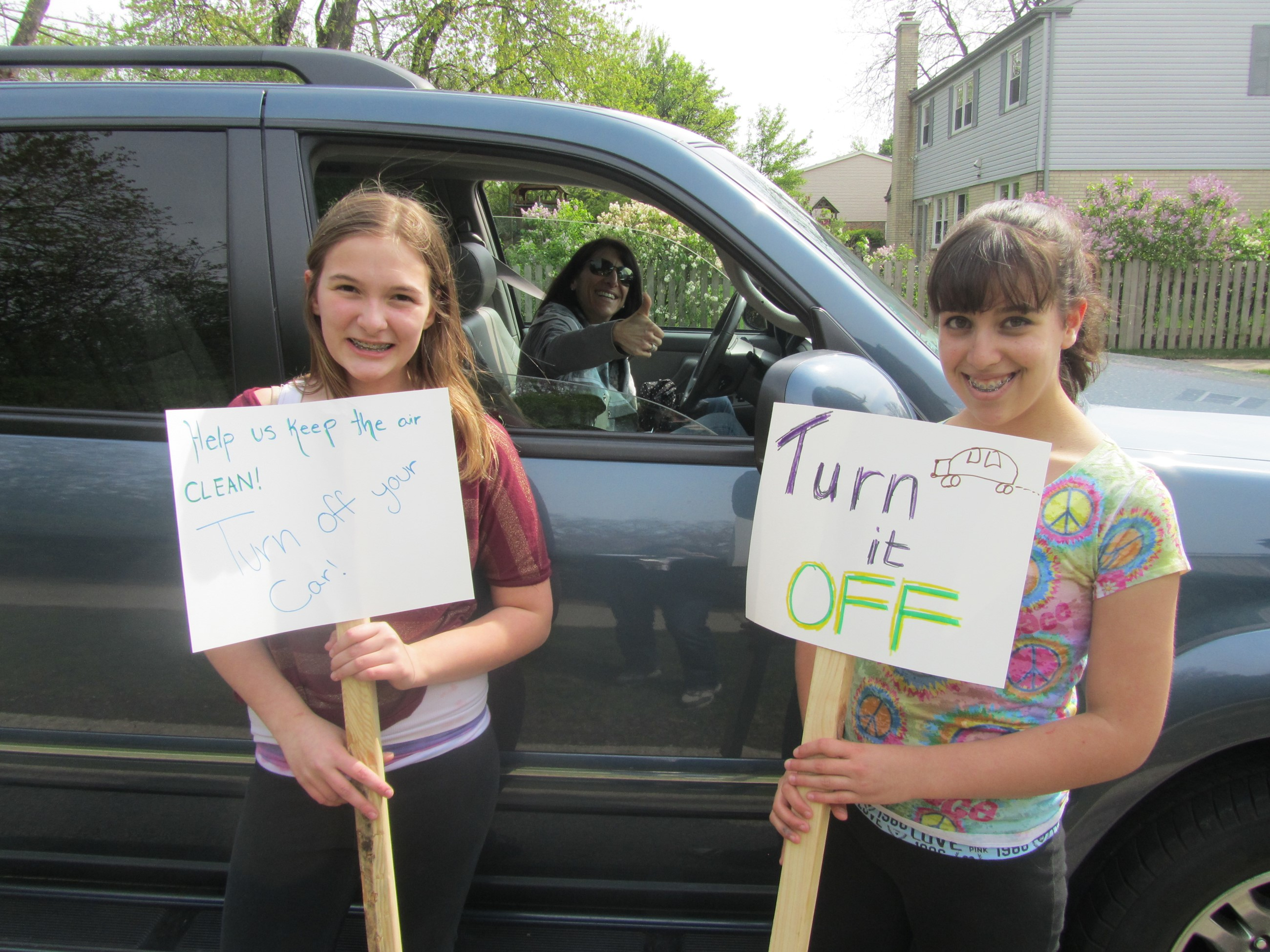 "Two girls holding signs encouraging parents to ""turn their cars off"""
